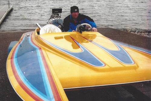 Sean driving a yellow and blue speedboat. He's wearing a backwards baseball cap and blue and black jacket