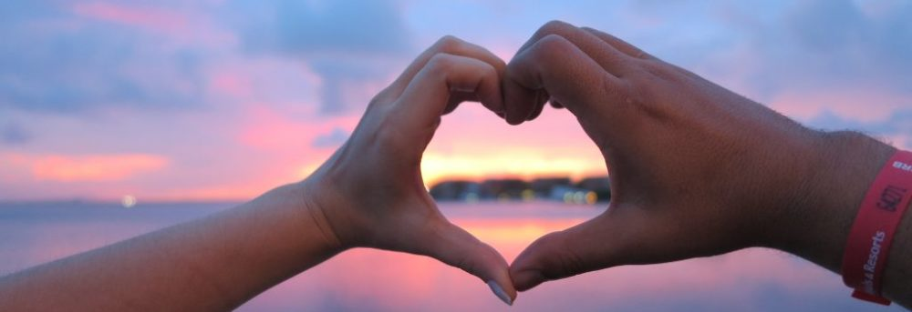 Two hands forming the shape of a heart with a sunrise sky behind them