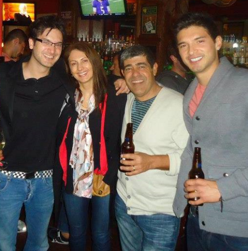 Daniel wearing glass in a black tshirt and jeans; Ana wearing a print shirt, black jacket with red stripe and jeans; Osvaldo wearing a white sweater jacket and jeans and Alejandro wearing a gray jacket and jeans