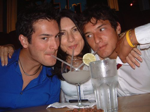 Daniel wearing a blue shirt; Ana wearing a white shirt; Alejandro wearing a white shirt, all sipping from the same margarita