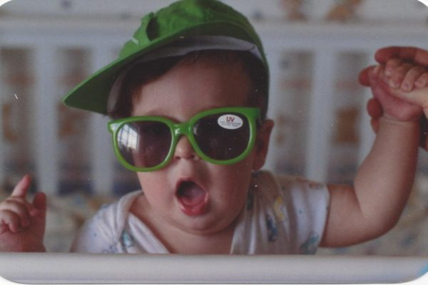 Jimmy standing his crib wearing a green hat and green sunglasses