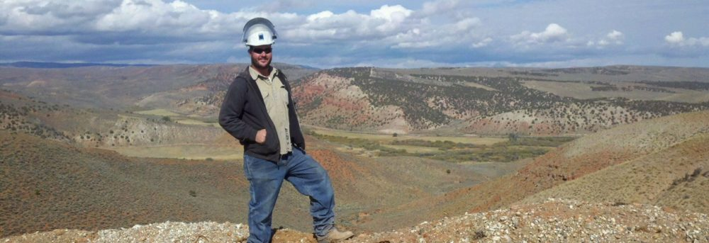 The author's son Jason wearing a white hardhat, dark jacket, light shirt and blue jeans standing on a hill in front of the pipeline