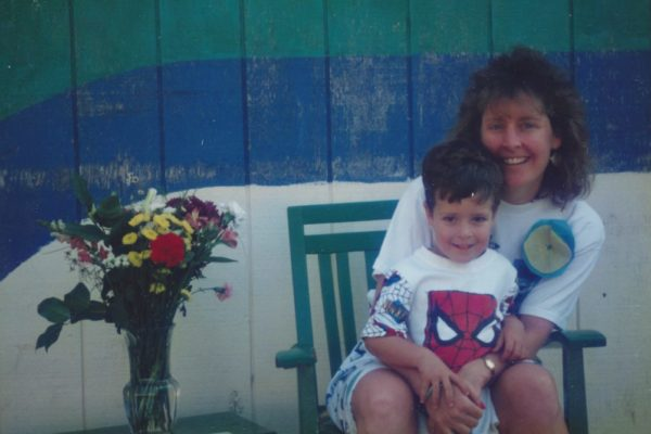 Margo and Jimmy in front of the shed at Fair Oaks Preschool. There are flowers on the table to their left. Jimmy is standing and wearing the top to his Spiderman pajamas; Margo is sitting on a green chair behind him wearing a white shirt