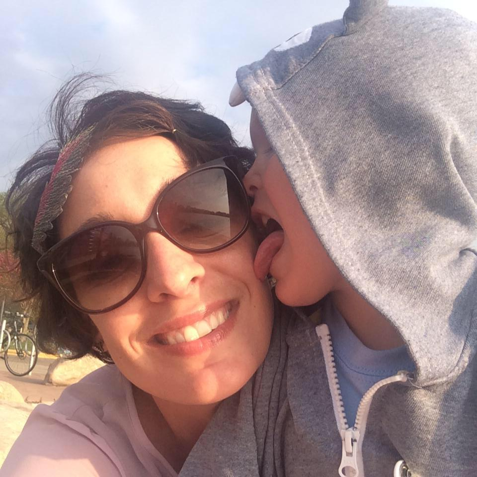 Erin Benson on the left wearing sunglasses and a light pink shirt; Sam is on the right wearing a gray hoodie and licking her face.