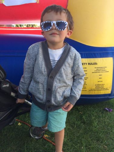 Sam as a young child wearing white and blue striped sunglasses, a gray sweater with darker gray strip around the edge, white t-shirt and green shorts.