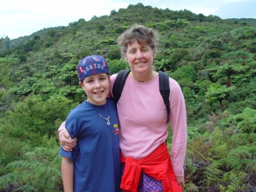 Jimmy and Margo in New Zealand standing in front a green hill. Jimmy is on the left wearing a Boston Red Sox baseball hat backwards and a blue t-shirt. Margo has a long sleeve pink shirt on with a red jacket tied around her waist. She has her right arm around Jimmy.