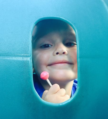 Same looking through an opening in a turquoise wall. He is smiling and holding a pink lollipop.