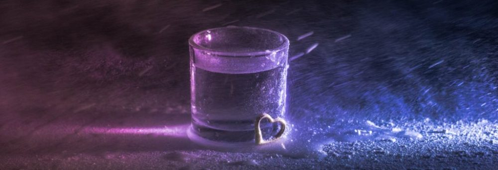 Glass of water with small heart leaning on the front right side lit with purple and blue light