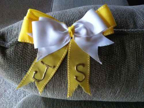 """Yellow hair box with """"J"""" and """"S"""" on the tails of the underlying bow with a white bow on top"""