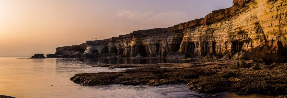 Beach on Cyprus at sunset with striated cliffs on the right side