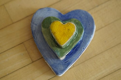 A ceramic heart sitting on a wooden table. The outer heart is painted blue; the middle heart is painted green and the smallest heart is painted yellow.