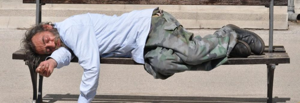 Homeless man laying on a bench asleep. The man is wearing a long sleeve light blue shirt and long gray green pants