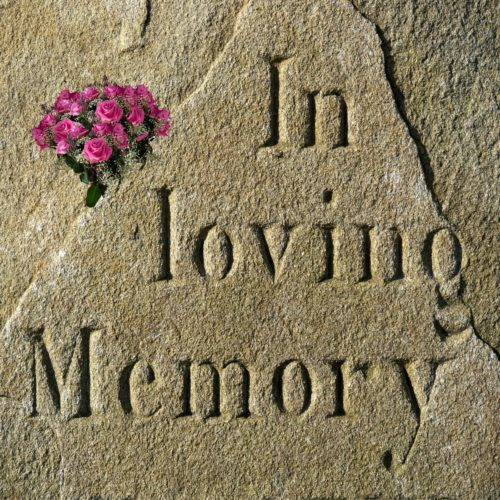 "The words In Loving Memory are written in sandstone with a small bouquet of flowers on the left just above the ""L"" in loving"