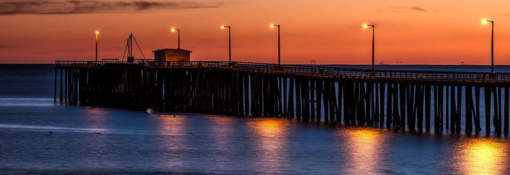 Pismo Beach pier at sunset. The sky is orange and water is blue-purple with orange reflections of the lights on the pier