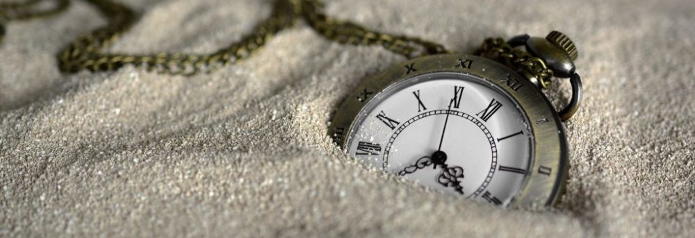 A pocket watch half buried in the sand