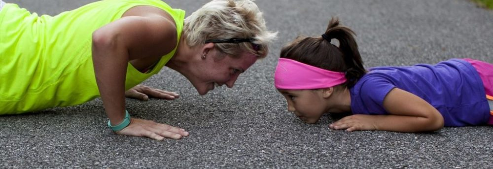 Woman and young girl doing pushups on a road or gravel path. The woman is on the left wearing a yellow tank top. She has blond hair. The young girl has dark hair in a pony tail and is wearing a pink headband and purple shirt.