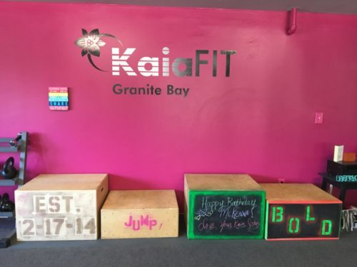 "KaiaFIT Granite Bay with the flower logo on a bright pink wall with four boxes below it. The first says ""Est. 2-17-14"". The second says JUMP. The third says Happy Birthday, McKenna. The fourth says BOLD."