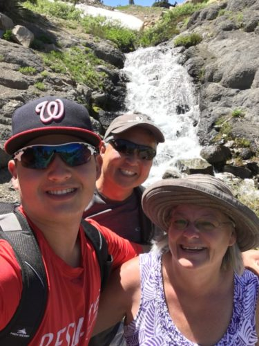 Tommy, Steve and Cindy in front of a waterfall. Tommy is wearing a Wenatchee baseball cap and a red shirt, carrying a backpack. Steve is wearing a baseball cap and sunglasses. Cindy is wearing a khaki hat, glasses and a purple print tank top