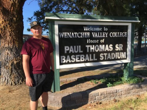 Tommy wearing his Wenatchee baseball hat, a maroon shirt and black shorts standing in front of a sign for the Paul Thomas senior baseball stadium