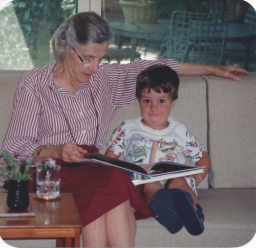 Mom on the left reading to Jimmy. Her head is down. She's wearing a striped button shirt and a maroon skirt. Jimmy is wearing Buzz Lightyear pajamas and is looking at the camera.