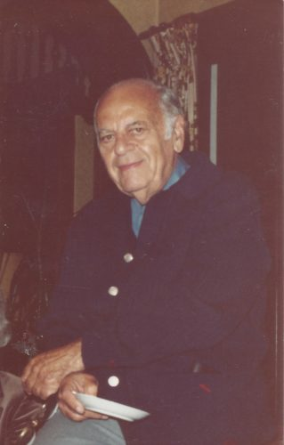 Dad in his 70s wearing a blue color shirt with a navy blue sweater with two gold buttons on it. He's tan with a rim of gray hair, smiling at the camera.
