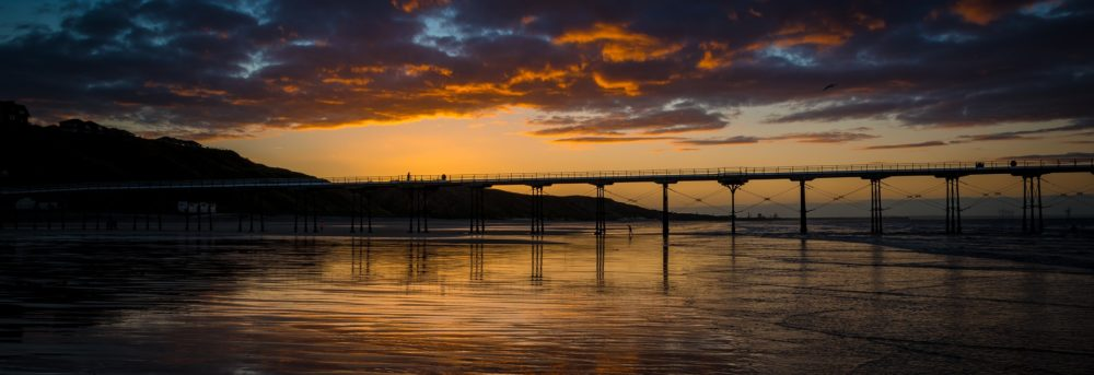 Bridge over a body of water against the backdrop of the sky just before the light fades at sundown.