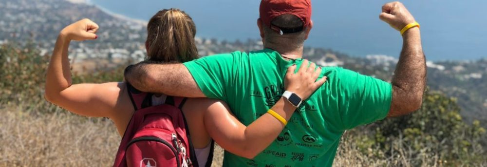 Molly and Dan standing with their backs to the camera overlooking the ocean near Santa Monica. Molly is making a muscle with her left arm and carrying a red Nike Stanford backpack. Dan is wearing a green shirt and red baseball cap and is making a muscle with his right arm.