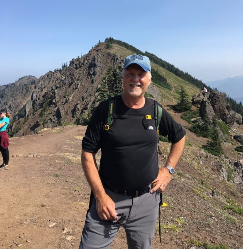 Gregg on hike wearing a black athletic short sleeved shirt, baseball cap, standing with his hands on his hips.