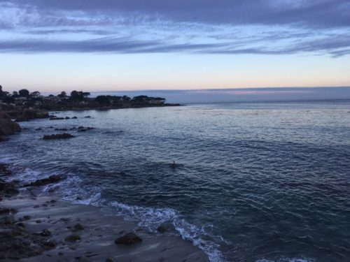 Pacific Grove beach at sunrise. Between the clouds and the ocean, there's a line of clear sky.