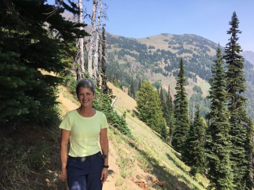 Karen on a hike wearing a yellow short sleeve shirt and blue pants. The trail, trees and mountain is behind her.