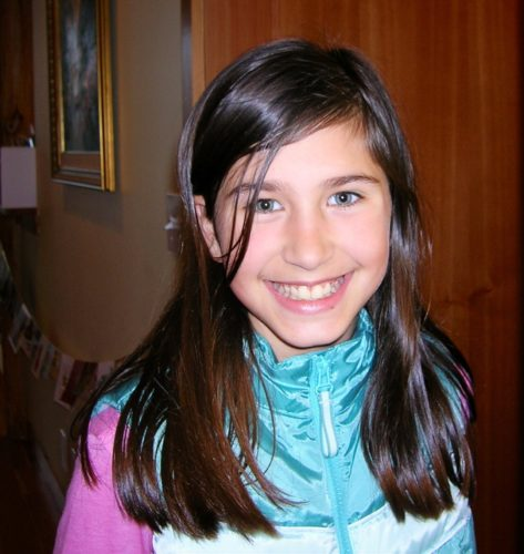 Katie wearing a big smile looking right at the camera. She has long brown hair parted on the side and is wearing a teal and pink athletic jacket.