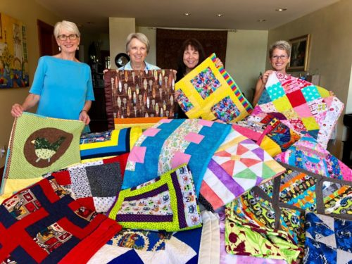 Katie's Comforters Guild -- three women involved with the program plus Karen on the right wearing glasses. In front of the four women are an array of brightly colored quilts.