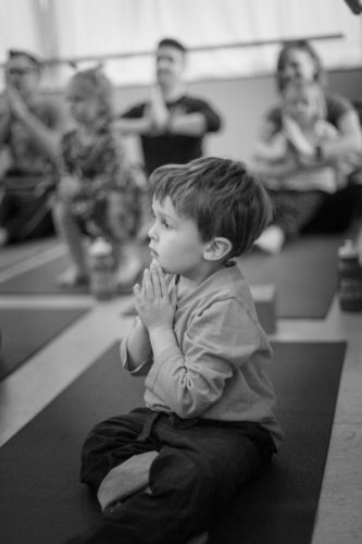 Black and white photo of Sam sitting cross legged with his hands in prayer doing yoga.