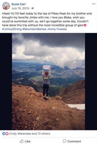 Susie standing on Pikes Peak wearing her JimmySTRONG shirt