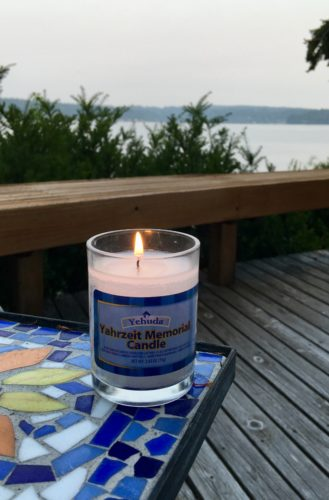 Lit yahrzheit candle for Katie sitting on blue, white and dark blue tile table on Karen's deck with view of the water beyond the low wall of the deck.