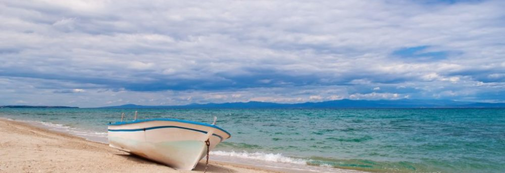 An old white rowboat with blue trim sitting on a sandy beach with blue ocean to the right and a cloudy blue sky above