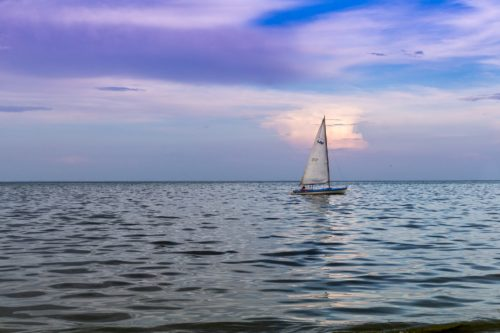 Sailboat off in the distance against a blue, white and purple sky.