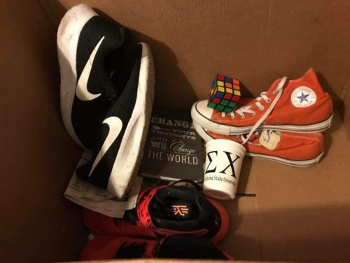 "A collection of Brandon's possessions including a pair of black and white Nike's, red hightop sneakers, a fraternity cup with an ""E"" and an ""X"" on it and a book"