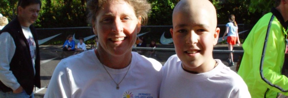 "Margo and Jimmy after a race in 2006. Margo is on the right wearing a long sleeve white t-shirt that says ""Portland Children's Museum"". Jimmy is on the right, bald from cancer treatment wearing a short sleeve white t-shirt with the number 3186 pinned to the front"