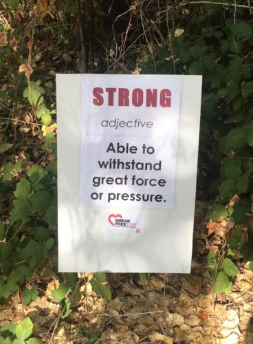 "Race sign on 10K course that says ""Strong, adjective. Able to withstand great force or pressure."""