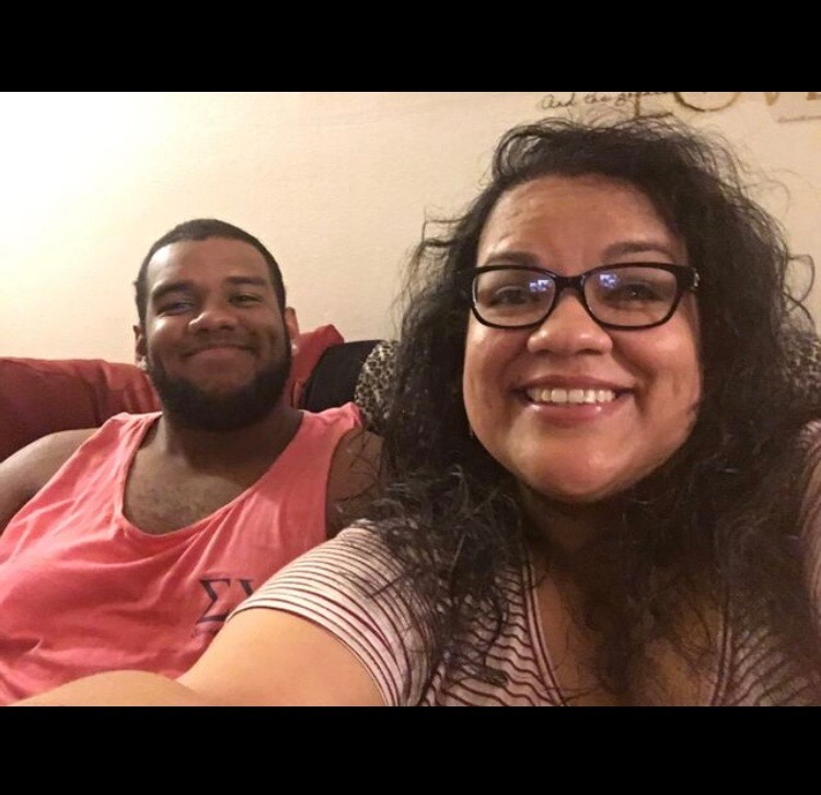 Brandon and Sarah. Brandon is on the left wearing a red-orange tank top. Sarah is taking the selfie. She's wearing a striped shirt and black frame glasses.