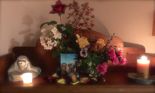Tilly's altar with a photo of her and Aimee on the bottom shelf, a vase of flowers behind the photo with a red red, candles on either side of the photo and flowers