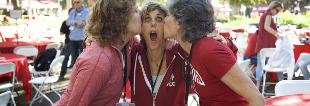 Margo, Debbie and Jennifer. Margo is on the left wearing a long sleeve red top and white shorts and is kissing Debbie's right cheek. Debbie is in the middle wearing a red Stanford zip up sweatshirt and has her mouth open. Jen is on the right wearing a short sleeve red Stanford t-shirt and tan shorts and she's kissing Debbie's left cheek