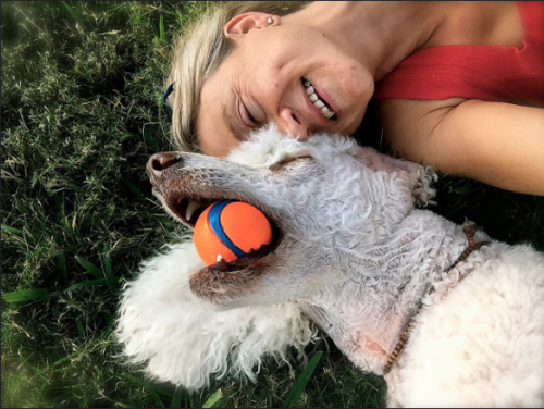 Aimee and Tilly laying on the grass. Tilly is on the left, on her back, holding an orange ball with a blue strip. Aimee is on the right with her blond hair pulled back wearing a red tank top