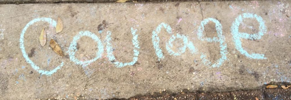 "The word ""courage"" is written in light blue chalk on the pavement"