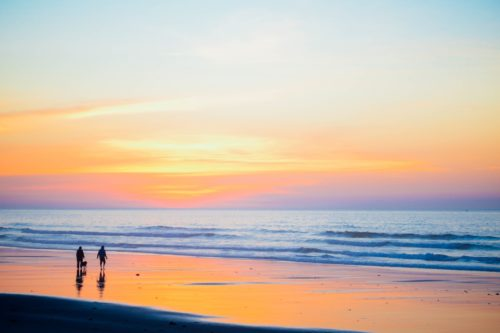Two people walking at the water line on a beach. The sun is setting the sky is blue, yellow and orange and is reflected in the wet sand.