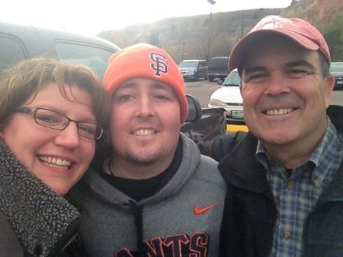 Heather is on the left wearing black rim glasses. Jimmy is in the middle wearing a SF Giants beanie and SF Giants gray sweatshirt with orange writing. Dan is on the right wearing a baseball hat, black jacket and plaid shirt.