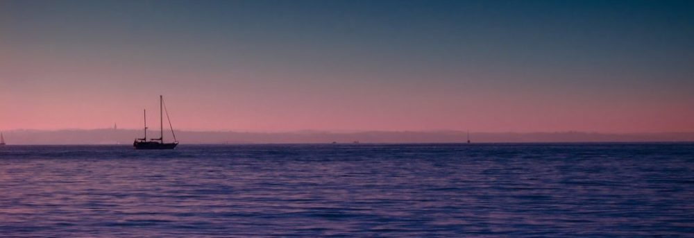 Sailboat off in the distance post sunset. The sky in the horizon line is pink; the ocean is violet and the sky is a darkening blue.
