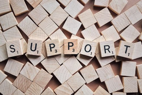 "The word ""SUPPORT"" is written in Scrabble tiles, sitting on turned over Scrabble tiles"
