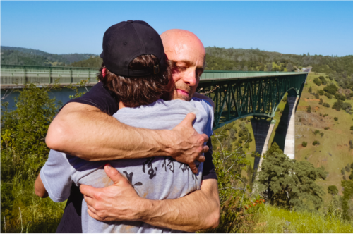 David Woods Bartley, wearing a navy short sleeve shirt, is hugging a man wearing a gray t-shirt with Asian characters on the back and a black baseball cap. The Foresthill bridge is behind them.